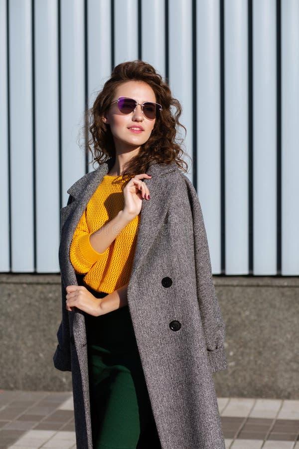 Uliczny portret jest ubranym okulary przeciwsłonecznych i żakiet elegancki model, pozuje blisko żaluzji przy miastem zdjęcia royalty free