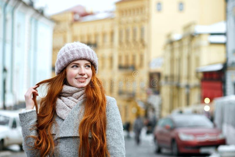 Uliczny portret uśmiechnięta rudzielec dziewczyna z długie włosy jest ubranym w obraz stock