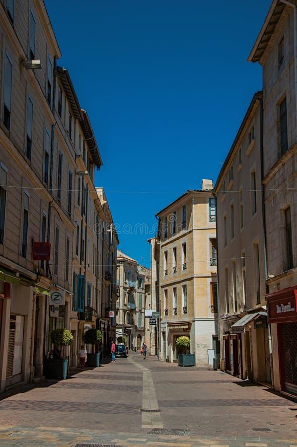 Uliczny widok z budynkami, sklepami i pogodnym niebieskim niebem w Nimes, obraz stock