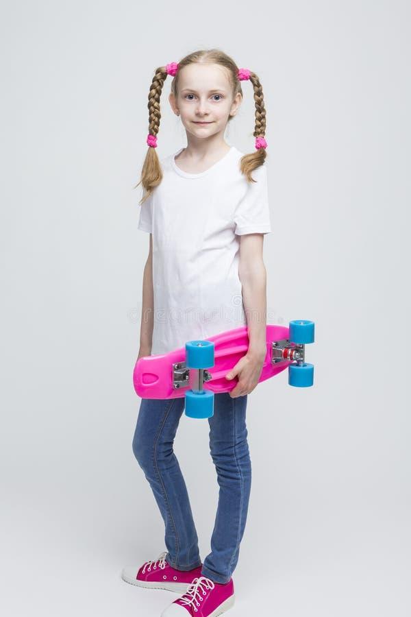 Ull długości portret Mała Kaukaska Blond dziewczyna z Ładnymi Pigtails Pozuje Z Różowym Pennyboard obrazy royalty free
