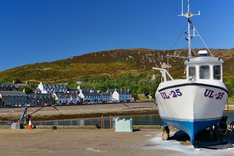 Ullapool, Шотландия - 27-ое мая 2012 - белая рыбацкая лодка на берег на пристани с гаванью, зданиями портового района и горной це стоковое фото