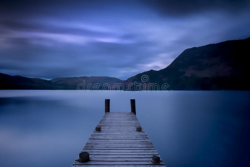 Ullswater Jetty. A small jetty pokes out into Ullswater Lake in England's Lake District in Cumbria. Shot at dusk with a long exposure. Unless otherwise stated stock image