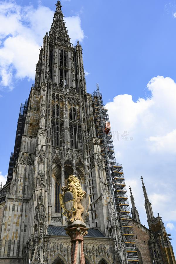 Ulm Minster, Tower of Ulm Cathedral, with golden lion pillar in front, royalty free stock photography
