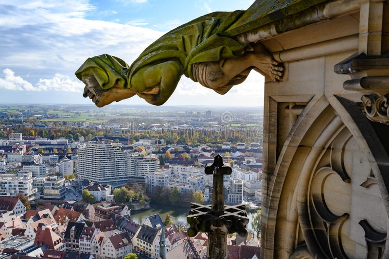 Gargoyle on tower of Ulm Minster overlooking City of Ulm - Baden-Wuerttemberg - and Neu Ulm - Bavaria, on River Danube, Germany royalty free stock image