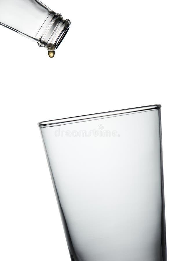 Ultima goccia della bevanda dalla sgocciolatura vuota della bottiglia nel vetro vuoto immagini stock