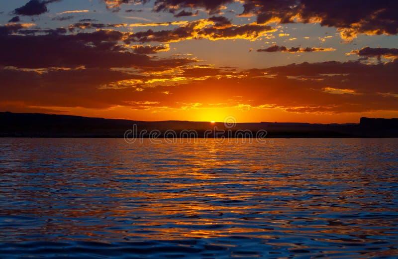 Ultima luce del Sun di giorno che scompare dietro una catena montuosa distante immagine stock