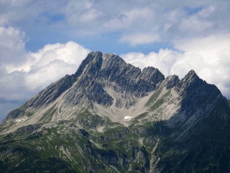 Ultima neve che si fonde su una montagna alpina dovuto riscaldamento globale immagini stock