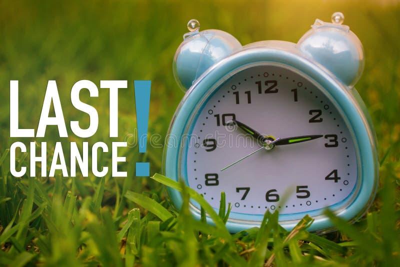 Ultima opportunità, concetto di affari - mandi un sms a mostrare l'ultima opportunità con un orologio su erba fotografia stock libera da diritti