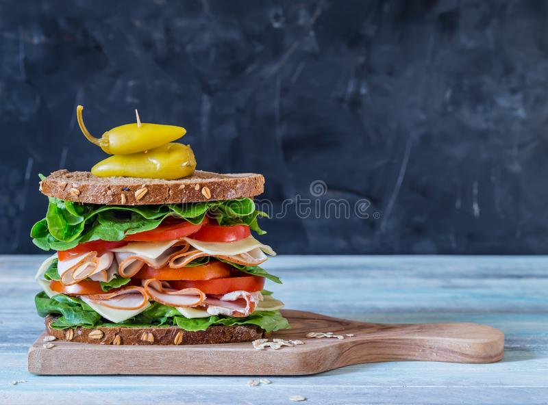 Ultimate Deli Sandwich on grey background. Ultimate Deli Sandwich with turkey pastrami lettuce and tomatoes on grey background with copy space stock image