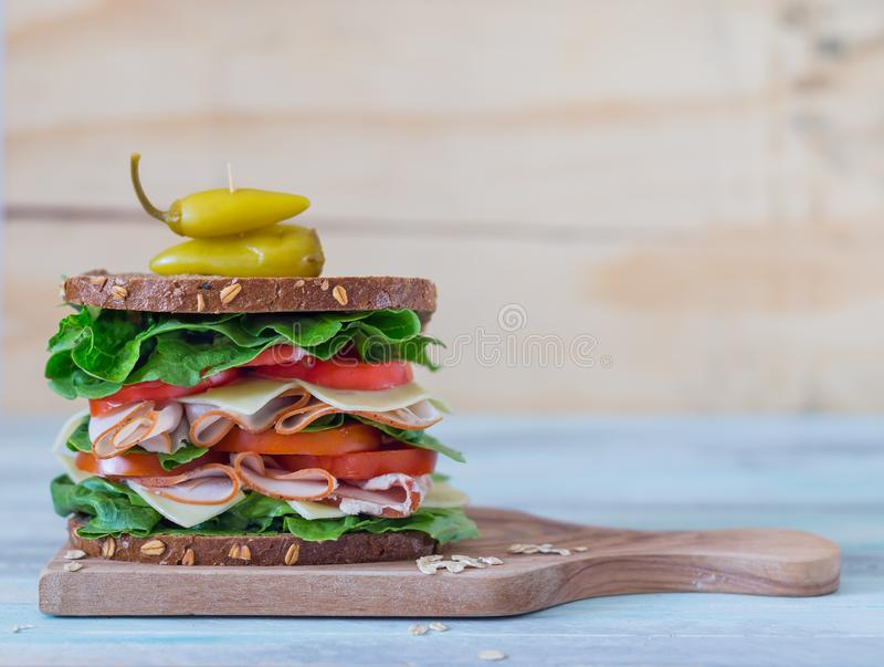 Ultimate Deli Sandwich on grey background. Ultimate Deli Sandwich with turkey pastrami lettuce and tomatoes on grey background with copy space royalty free stock image