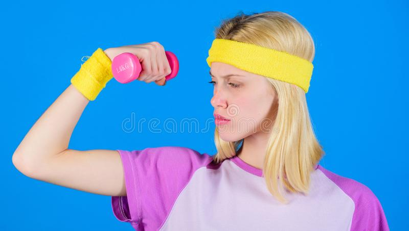 Ultimate upper body workout for women. Fitness concept. Girl exercising with dumbbell. Fitness instructor hold little. Dumbbell blue background. How to get royalty free stock images