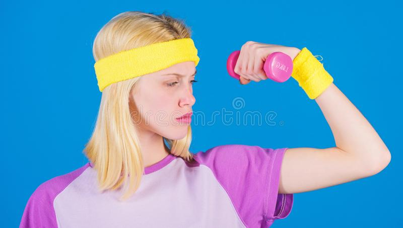 Ultimate upper body workout for women. Fitness concept. Girl exercising with dumbbell. Fitness instructor hold little. Dumbbell blue background. How to get stock photography
