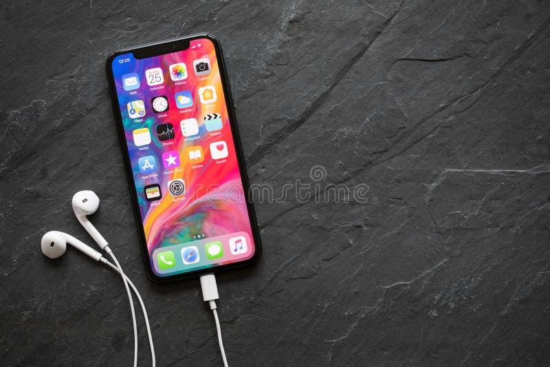 Ultimo iPhone X della generazione con le cuffie immagini stock
