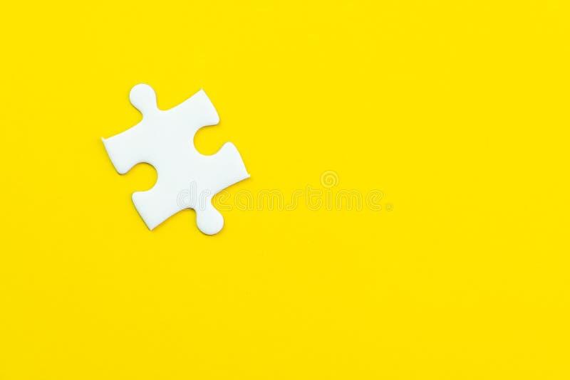 Ultimo soltanto un puzzle mancante su fondo giallo solido usando come associazione della cosa importante o lavorando insieme al s fotografia stock