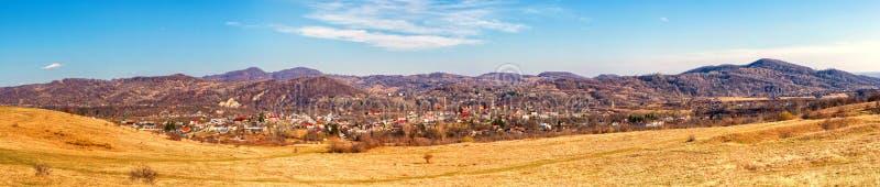 Ultra breed panorama van weide met stadshuizen en heuvels op de achtergrond stock fotografie
