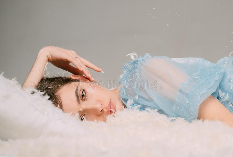 An ultra light and soft touch. Cute girl relaxing on feather bed pillow and mattress. Young woman in sleep wear. Pretty royalty free stock photo