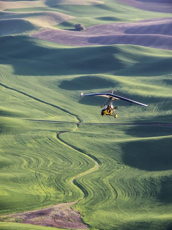 Ultra-light vliegtuigvliegen over tarwegebieden op de rollende heuvels royalty-vrije stock foto's