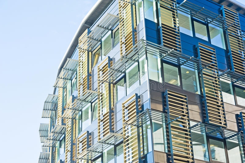 Ultra-modern building: advanced design. An image of an ultra-modern building constructed largely of glass and metal and with movable shutters stock photos