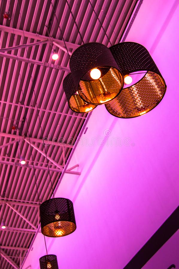 Ultra-modern loft style in purple toned color decorative lamps and lampshades hang on long rope, industrial ceiling, interior stock photos