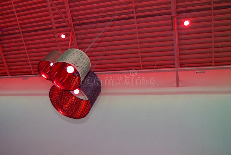 Ultra-modern loft style in red toned color decorative lamps and lampshades hang on a long rope, industrial ceiling, interior royalty free stock images