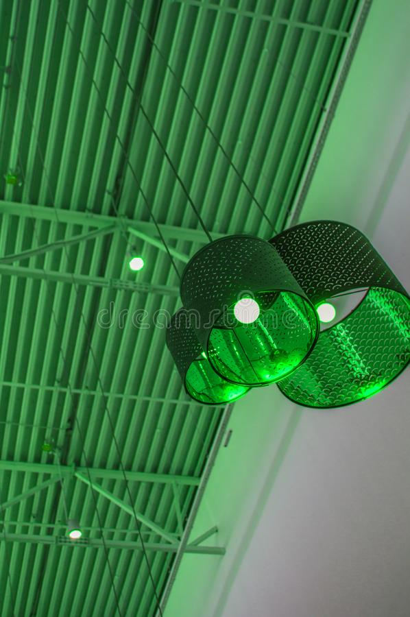 Ultra-modern style in green toned color decorative lamps and lampshades hang on long rope, industrial ceiling, interior design. Vertical shot, decoration royalty free stock image