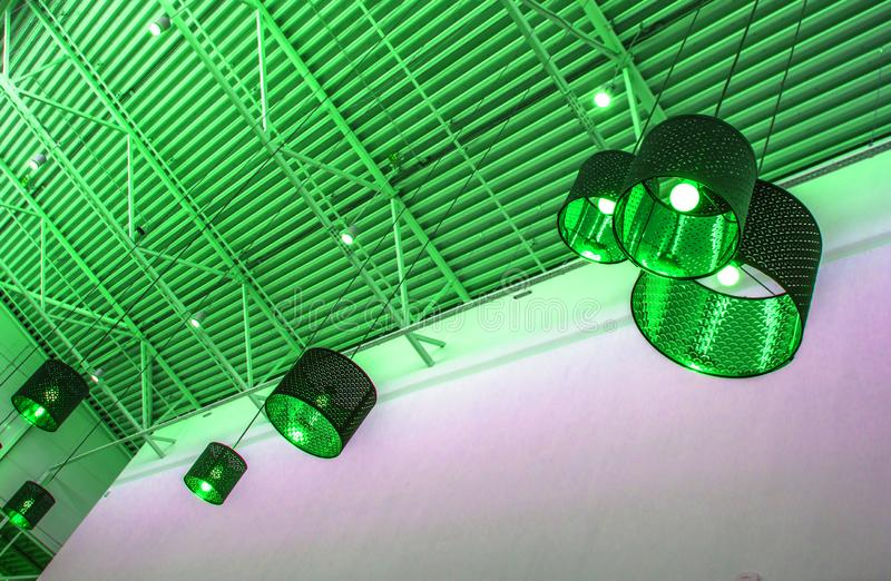 Ultra-modern style in green toned color decorative lamps and lampshades hang on long rope, industrial ceiling, interior design. Decoration, tinted, effect royalty free stock images