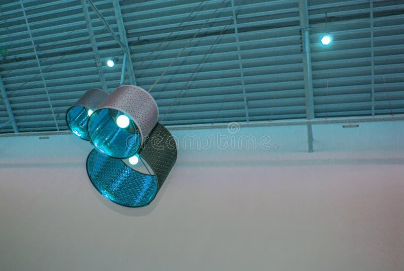 Ultra-modern zolderstijl in blauwe gestemde kleuren decoratieve lampen en de lampekappen hangen op lange kabel, industrieel plafo stock afbeelding