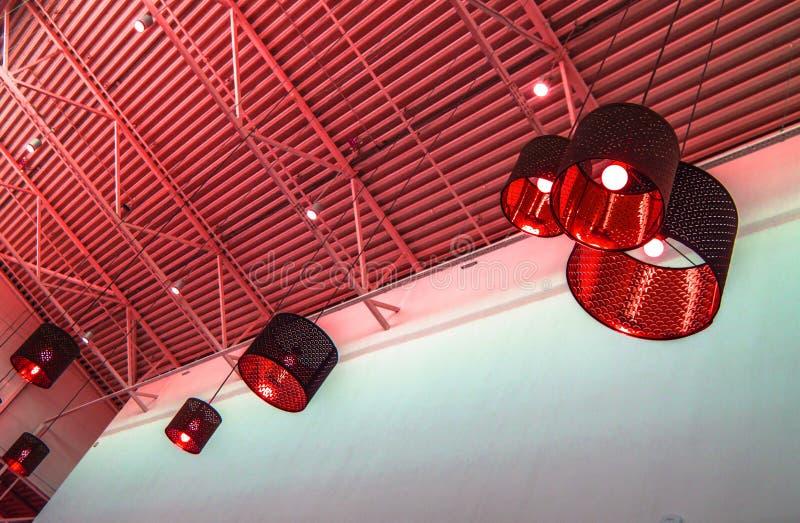 Ultra-modern zolderstijl in rode gestemde kleuren decoratieve lampen en de lampekappen hangen op een lange kabel, industrieel bin stock fotografie