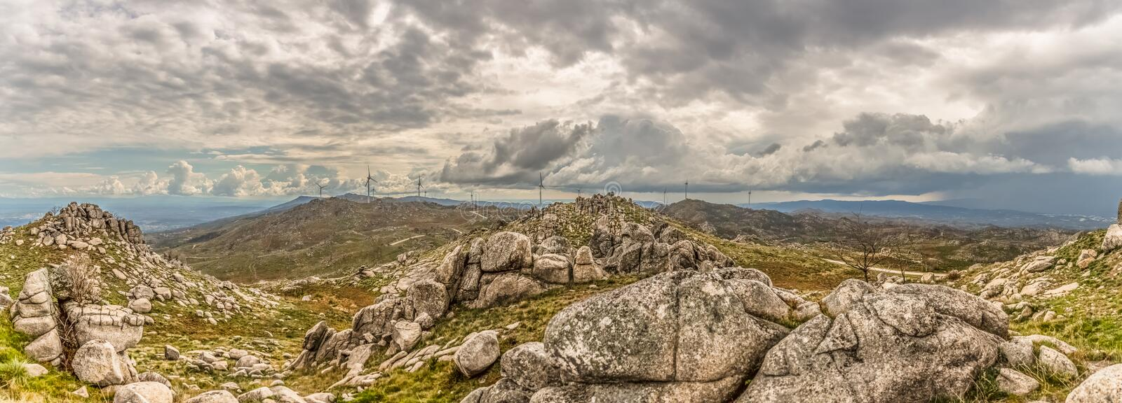 Ultra panoramic view at the Caramulo Mountains, and wind turbines on top of mountains and dramatic sky as background stock photo