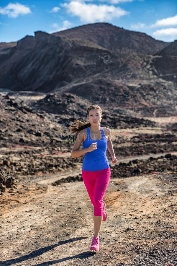 Ultra running trail runner woman on mountain run in rocky landscape training in warm and dry outdoor weather. Asian girl jogging. Outside, motivation and health royalty free stock image