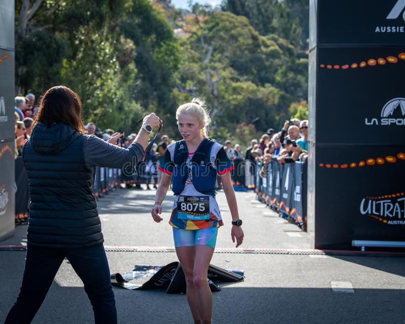 Ultra-Trail Australia UTA11 race. Runner Paige Penrose, over all winner of womens event, takes medal at the finish line stock image