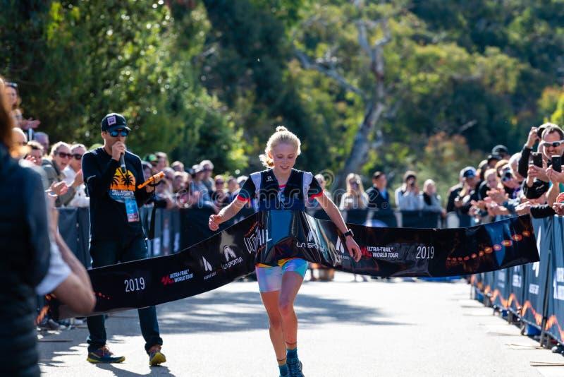 Ultra-Trail Australia UTA11 race. Runner Paige Penrose, winner of the womens event, crosses the finish tape at the finish line. Blue Mountains, Australia - April stock image