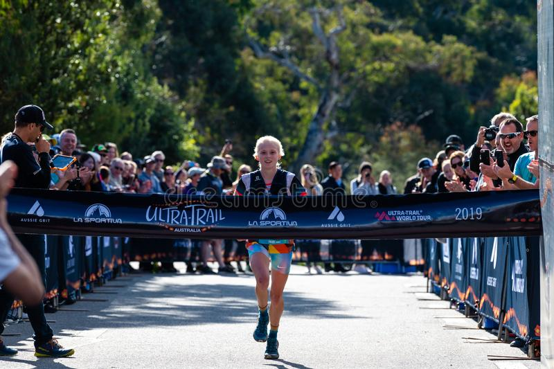 Ultra-Trail Australia UTA11 race. Runner Paige Penrose, winner of the womens event, at the finish line. Blue Mountains, Australia - April 16 2019: Ultra-Trail royalty free stock images