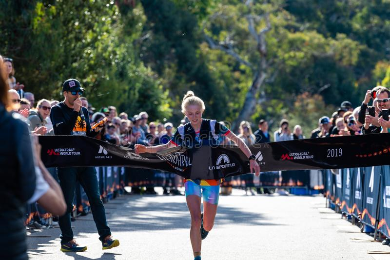 Ultra-Trail Australia UTA11 race. Runner Paige Penrose, winner of the womens event, takes the tape at the finish line. Blue Mountains, Australia - April 16 2019 royalty free stock photo