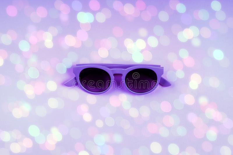 Ultra violet sun glasses on backdrop with bokeh. Ultra violet sun glasses on purple background with colorful light bokeh. Minimal trendy festive color flat lay royalty free stock images