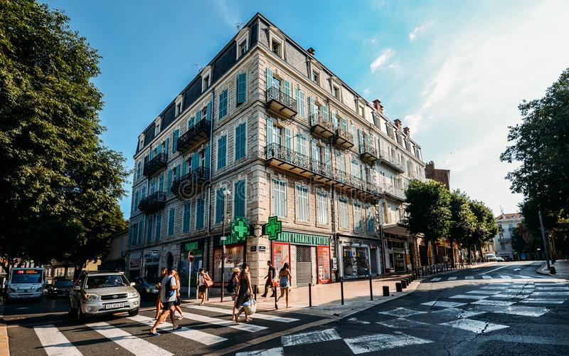 Ultra wide angle view of pedestrians crossing a street across from a typical Provencal style building. Antibes, France - July 8, 2018: Ultra wide angle view of stock photography