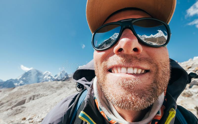 Ultra-wide lens angle portrait shot of high altitude mountain smiling unshaven happy hiker in baseball cap with snow peaks and royalty free stock image