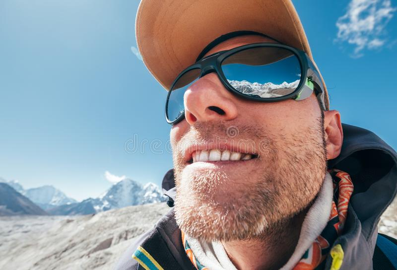 Ultra-wide lens angle portrait shot of high altitude mountain smiling unshaven happy hiker in baseball cap with snow peaks and. Mountain range beside him and royalty free stock image