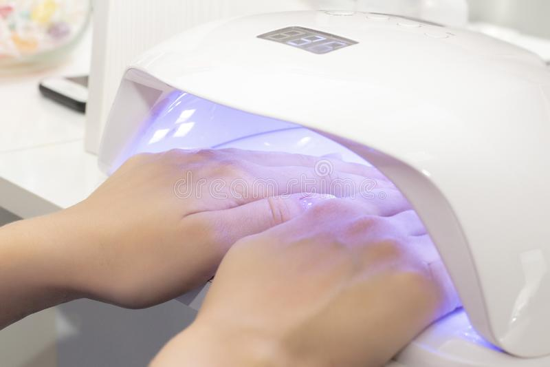 ULTRAFIOLETOWA lampa dla suszyć lakier dla dwa ręk dziewczyna suszy gumilakę na dwa rękach w lampie obrazy stock