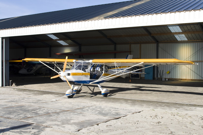 Ultralight plane in hangar. Yellow and blue ultralight plane in hangar royalty free stock image