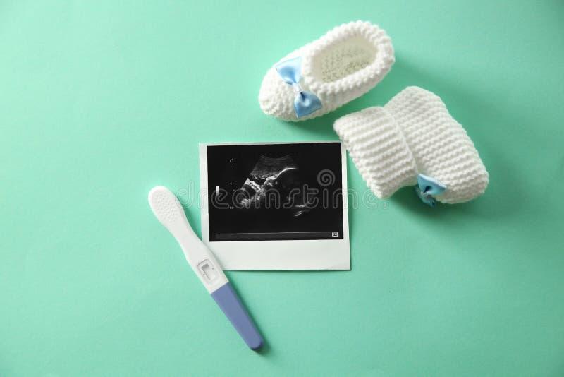 Ultraljudbilden, behandla som ett barn skor och graviditetstestet på färgbakgrund arkivbild