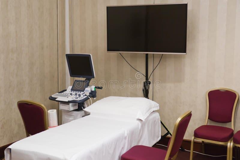 Ultraljuds- utbildande avläsande hörn, extra bildskärm, säng, stol arkivbild