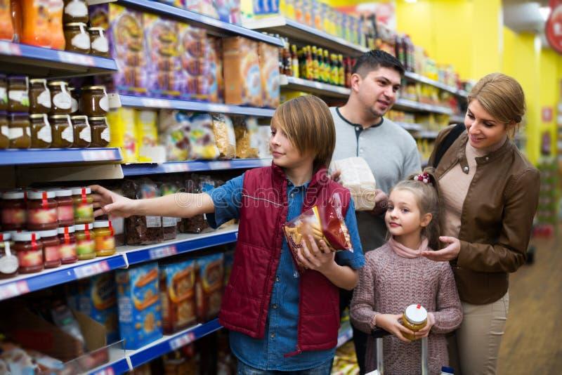 Ultramarinos de compra de la familia en supermercado fotos de archivo