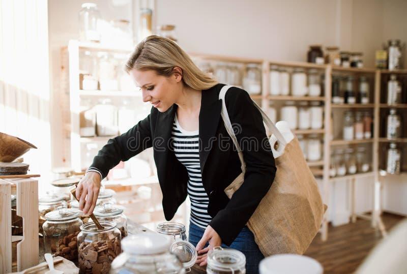 Ultramarinos de compra de una mujer feliz joven en la tienda inútil cero fotografía de archivo