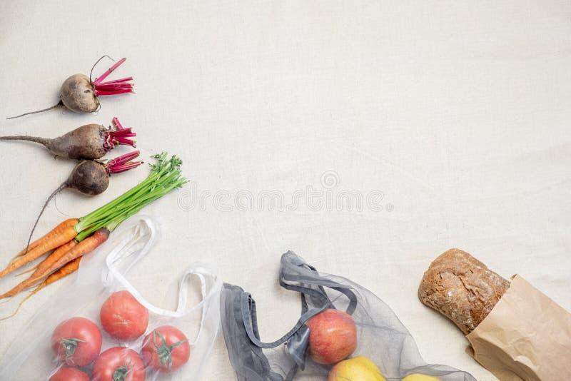 Ultramarinos en bolsos reutilizables en el lino o el fondo natural del cáñamo, visión superior imagen de archivo