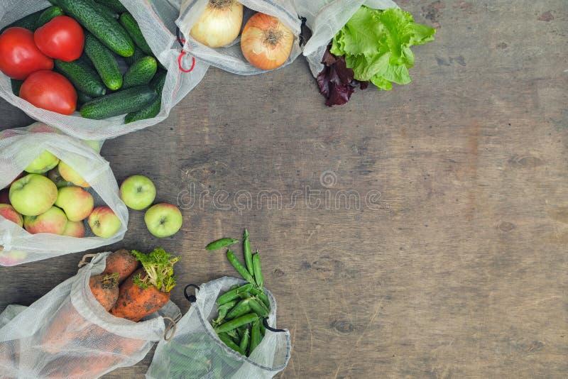 Ultramarinos orgánicos frescos en bolsos reciclados reutilizables de la producción de la malla en fondo de madera con el espacio  foto de archivo