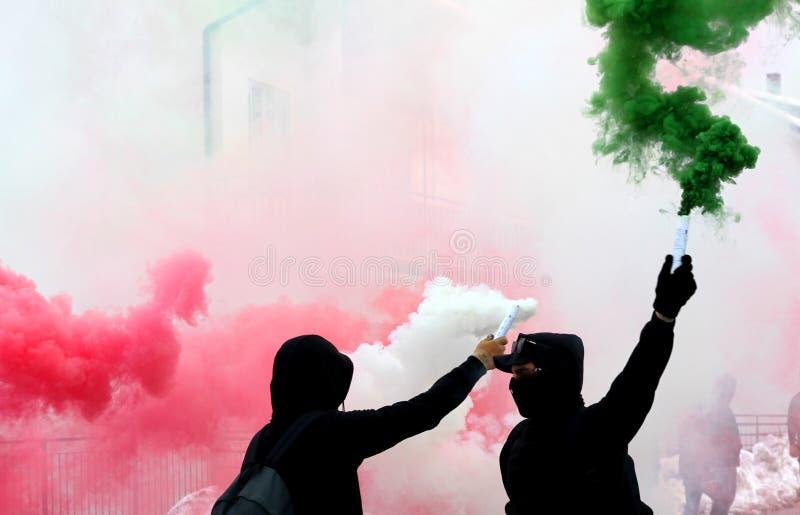 Ultras aviva con blanco y verde rojos del humo vestidos en negro imagenes de archivo