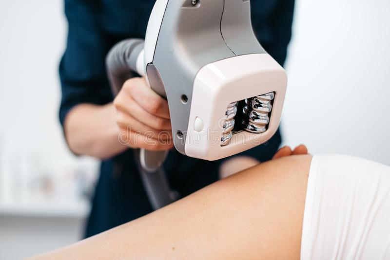 Ultraschallhohlraumbildung mashine in den Händen des Kosmetikers Weiche Farben Frau bekommt die AntiCellulitebehandlung lizenzfreie stockfotografie