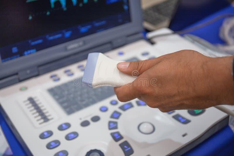 Ultraschallscanner in Doktorhand für medizinische Diagnosen mit Computerausrüstung lizenzfreie stockfotos