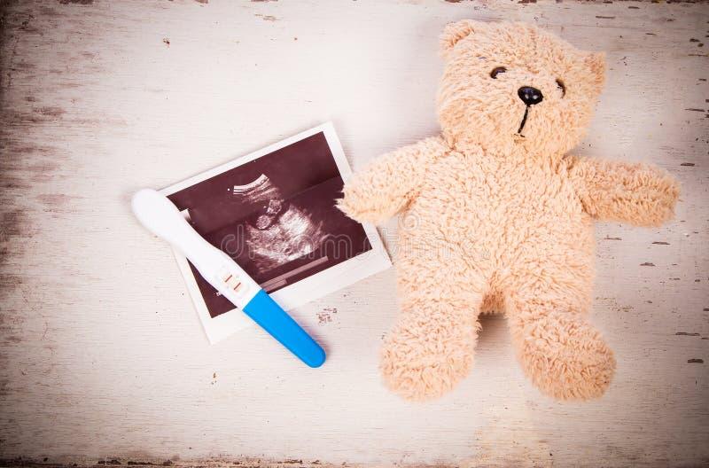 Ultrasone klank met zwangerschapstest en babyteddybeer stock fotografie